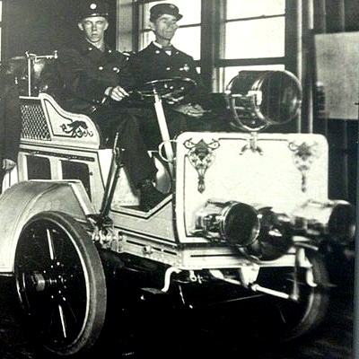 Painted ornaments on early motorized fire engine.