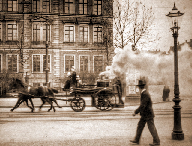 Early steamer on city street.