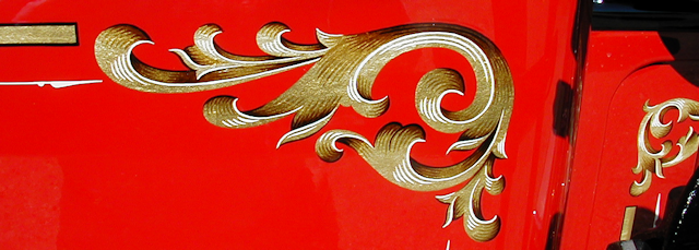 Close-up of hand painted gold leaf scroll on an Ahrens-Fox hose body.